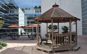 Spacious interior courtyard features a gazebo and market-style tables with umbrellas for relaxation or events